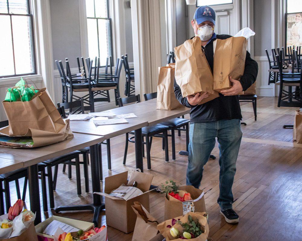 A volunteer prepares to deliver food.